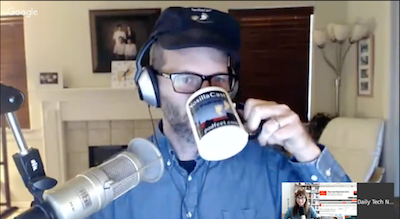 Tom wearing a NosillaCast had and drinking from a NosillaCast mug