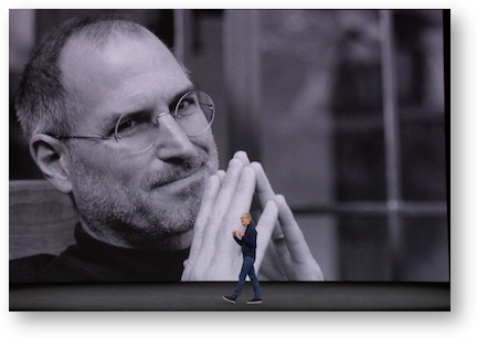 Tim walking in front of huge steve jobs