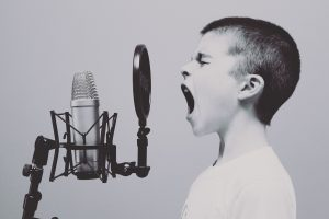 Young boy screaming into a mic