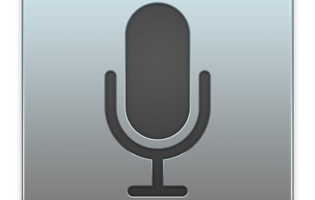 dark grey microphone on light grey background indicating dictation